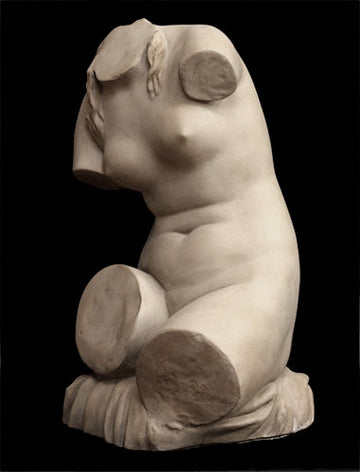 photo with black background of plaster cast sculpture of female torso seated