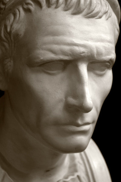 closeup photo with black background of plaster cast bust sculpture of a man, namely Antiochus III, with headband and clothing on the square bust