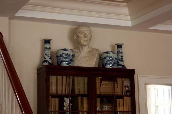 photo of plaster cast sculpture of male head of Cicero with squared bust and white and blue vases on a dark wood bookcase against a tan wall and staircase railing to the left