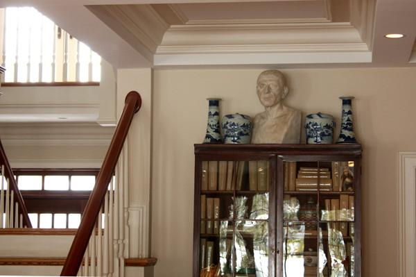 photo of plaster cast sculpture of male head of Cicero with squared bust and white and blue vases on a dark wood bookcase against a tan wall and staircase to the left