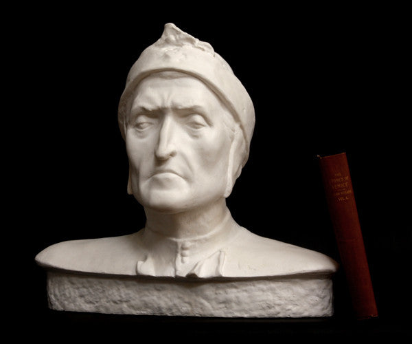 photo of plaster cast bust sculpture of Dante Alighieri with cap and high-necked robe with red book leaning against right side on black background