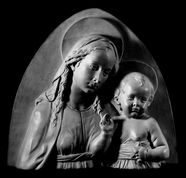 Photo of plaster sculpture of Madonna and Child on a black background