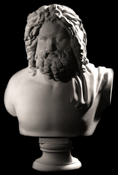 Photo with black background of plaster cast sculpture of male bust, namely the god Zeus, with curly hair and beard and robe over left shoulder
