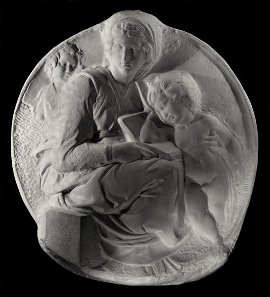 photo of plaster cast sculpture relief of the Madonna sitting with the baby Jesus beside her leaning on a book on her lap on a black background