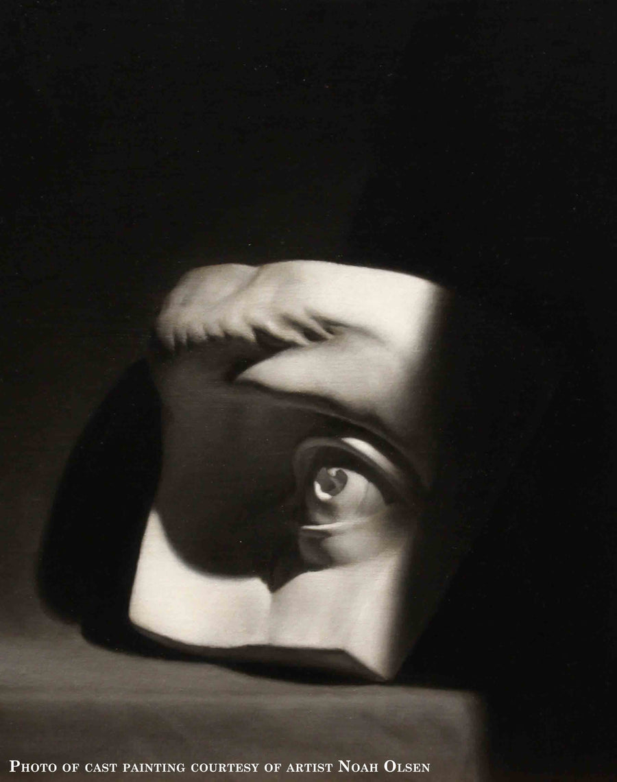 Photo of cast painting of plaster cast of eye on a gray shelf and black background