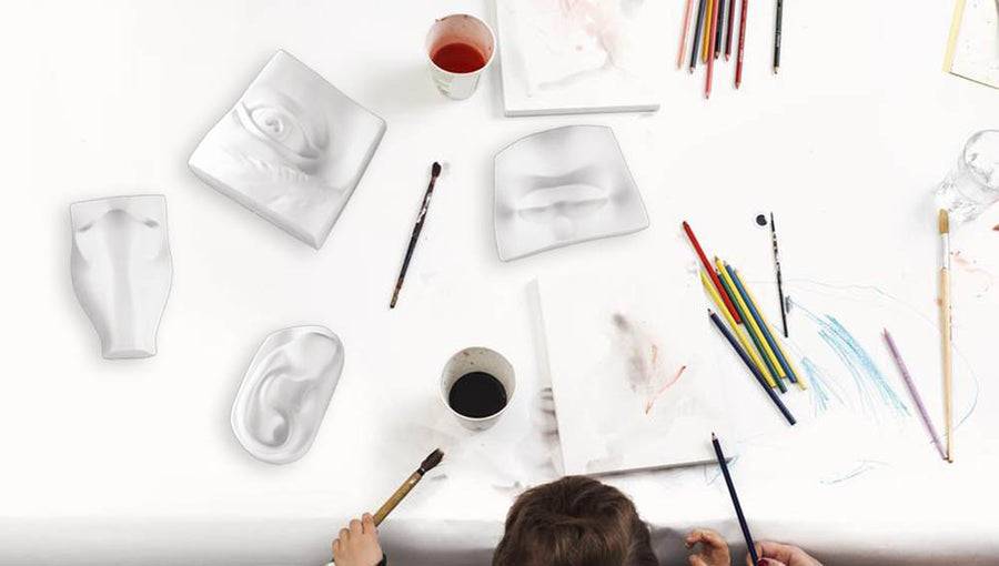 Photo of the top of a white work space with the head of a child drawing with a collection of plaster sculptures, paints, brushes, and paper