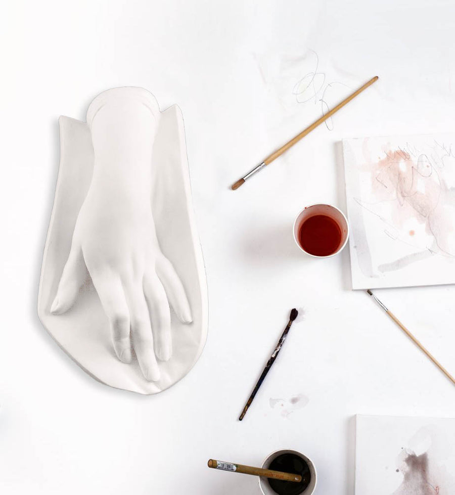 Photo of a plaster cast of a female hand on a white table with paintbrushes, paints, and paper