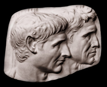 photo of plaster cast sculpture relief of two male heads with a black background