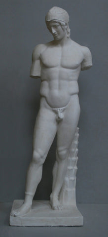 photo of plaster cast of sculpture of nude male without arms and wearing a helmet with a supporting tree trunk, on a gray background