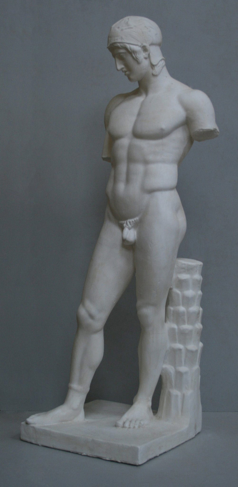 photo of plaster cast of sculpture of nude male, namely the god Ares, without arms and wearing a helmet with a supporting tree trunk, on a gray background