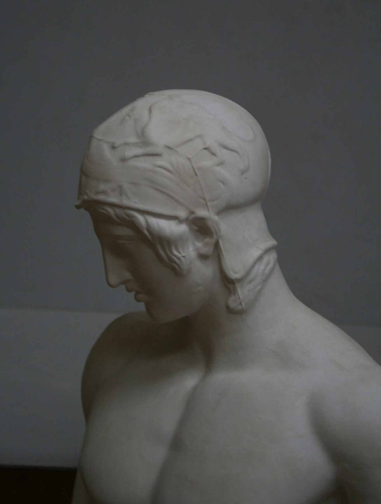 photo of plaster cast of sculpture of nude male without arms and wearing a helmet on a gray background