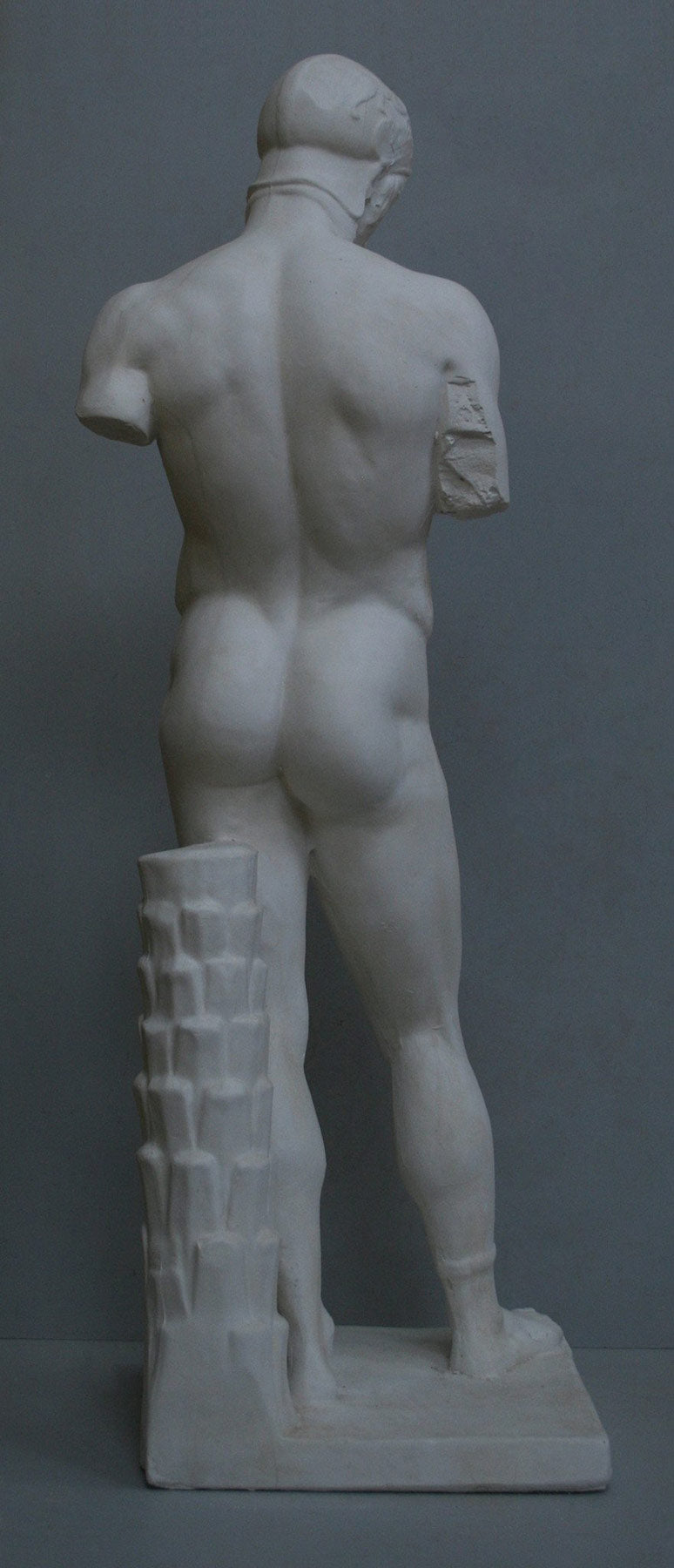 photo of back of plaster cast of sculpture of nude male without arms and wearing a helmet with a supporting tree trunk, on a gray background