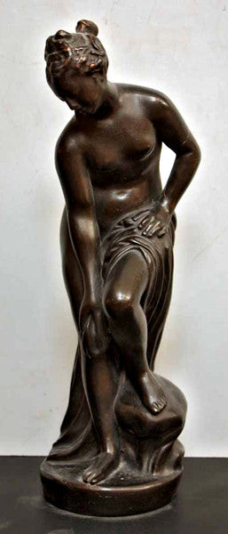 photo of bronze-colored plaster cast of sculpture of partially nude female, namely Venus, leaning forward to wash her left leg, placed on a dark table against white background