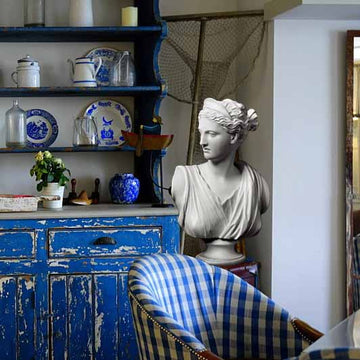 Photo of white plaster cast of sculpture bust of female goddess Diana with drapery and crown and up-do in a kitchen with blue hutch and chair