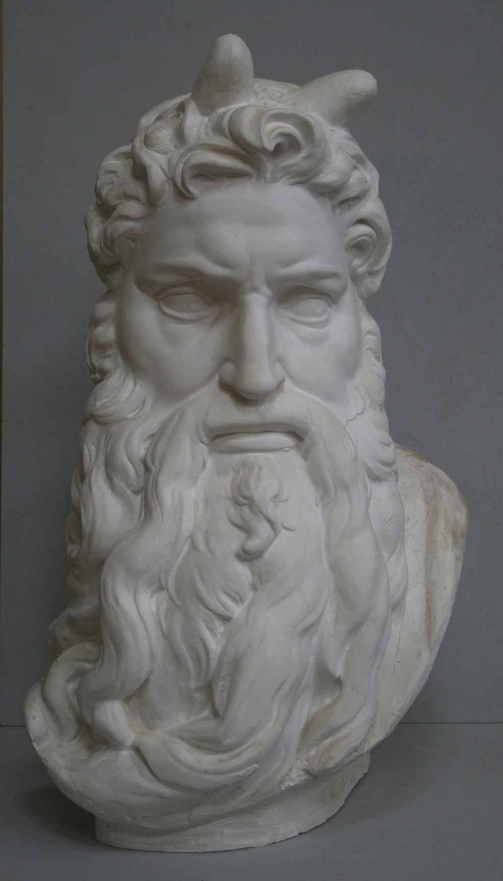 photo of plaster cast bust of man with curly hair and so-called horns and long beard on gray background