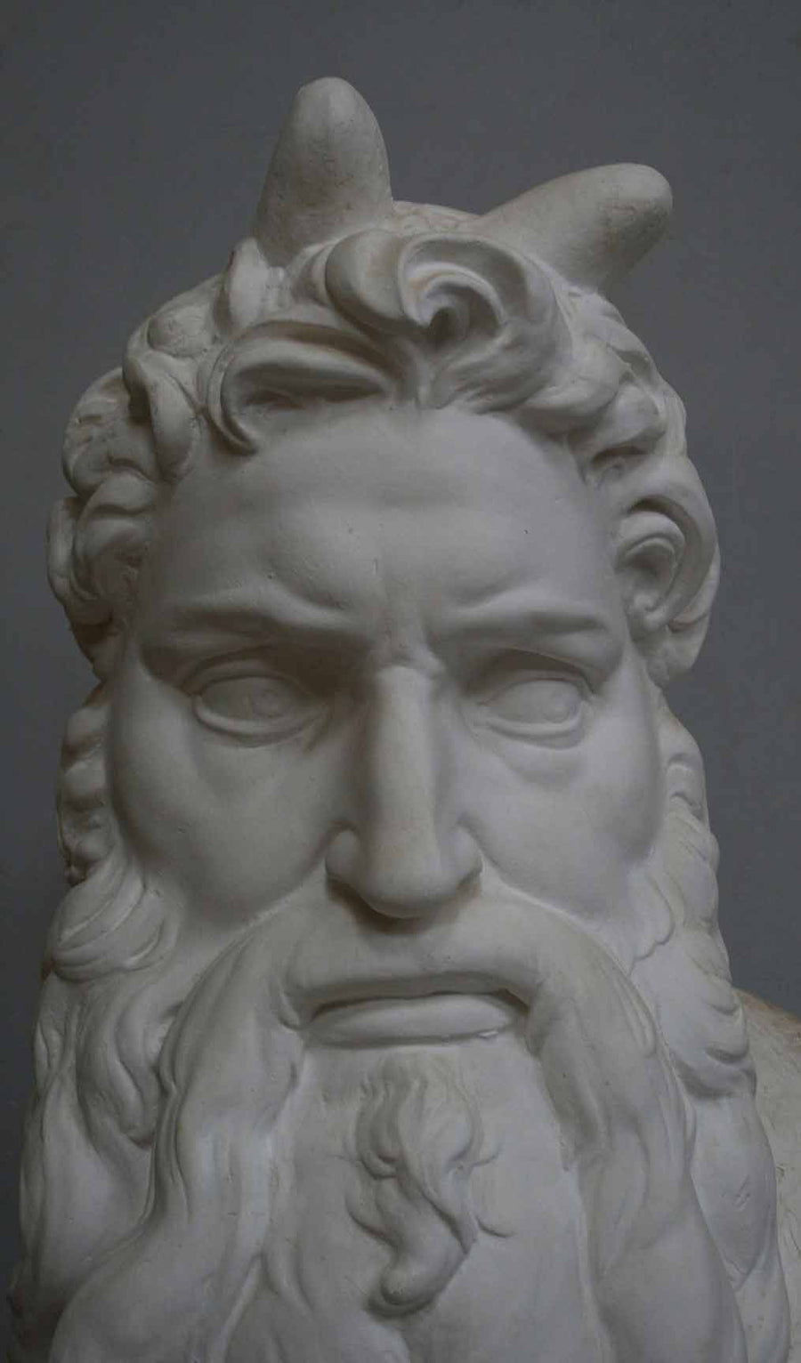 closeup photo of plaster cast bust of man, namely Moses, with curly hair and so-called horns and long beard on gray background