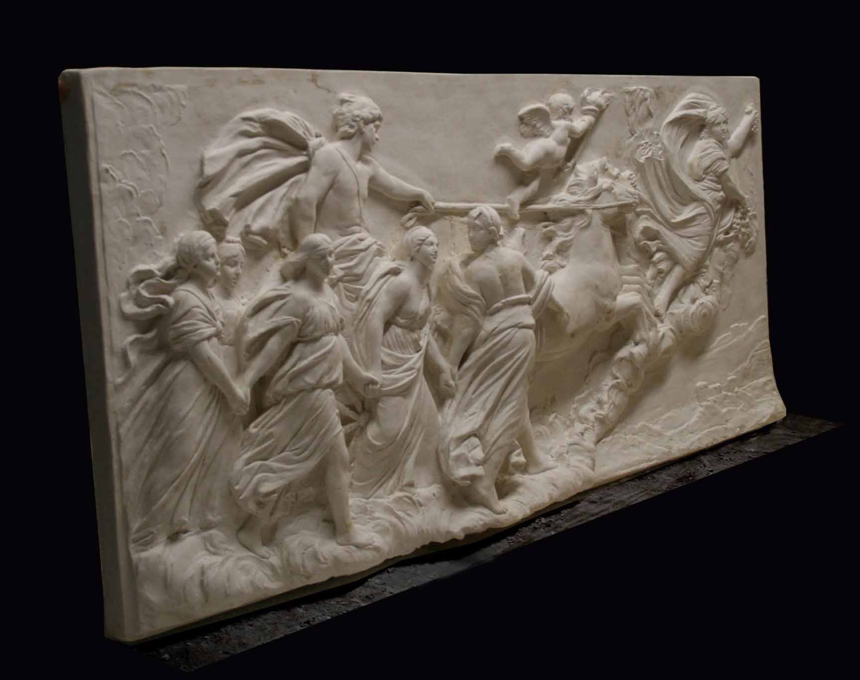 photo of a plaster cast relief of a woman flying and leading a chariot with a man pulled by horses towards the right while a cherub and other women fill the scene, on a black background