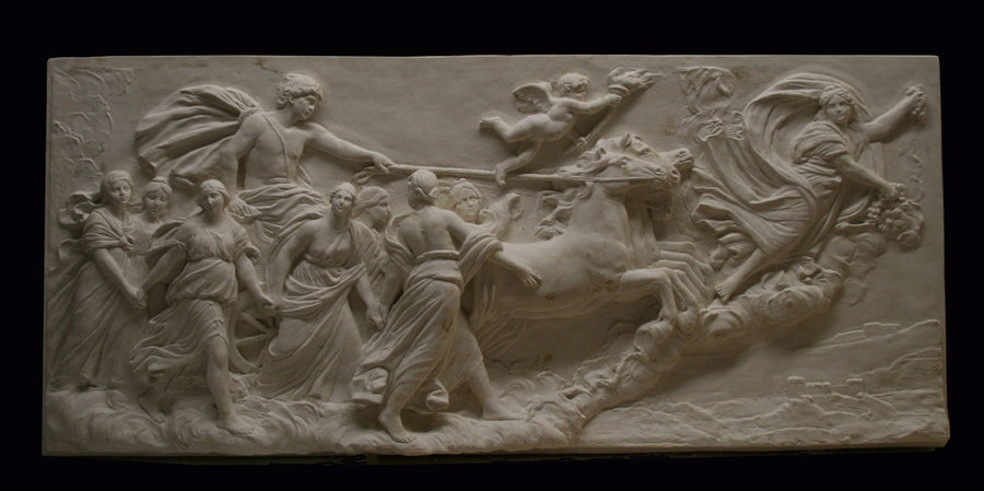 photo of a plaster cast sculpture relief of a woman flying and leading a chariot with a man pulled by horses towards the right while a cherub and other women fill the scene, on a black background