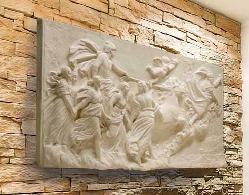 photo of a plaster cast sculpture relief of a woman, namely the goddess Aurora, flying and leading a chariot with a man pulled by horses towards the right while a cherub and other women fill the scene, on a tan brick wall