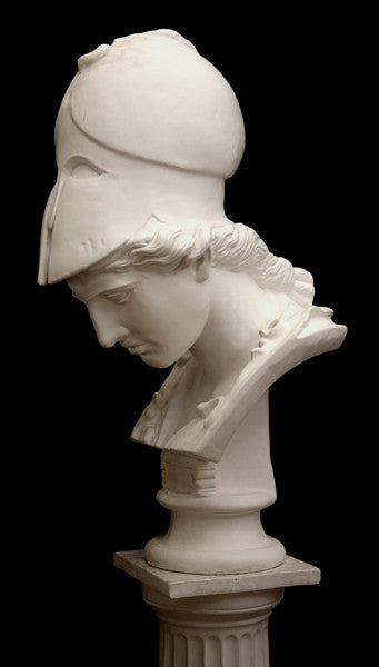 photo of plaster cast sculpture bust of female head, namely the goddess Minerva, with a helmet and looking down and placed on a pedestal with black background