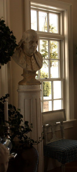 Photo of male bust sculpture on tall pedestal next to a window in a dining room