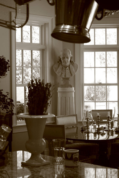 Sepia-toned photo of male bust sculpture on tall pedestal in between two windows in a dining room
