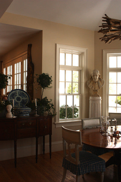 Photo of male bust sculpture on tall pedestal in between two windows in a dining room