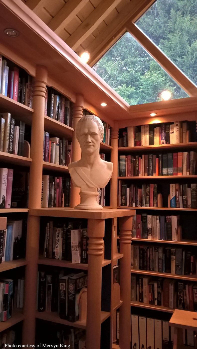 photo of two walls of a library filled with books and skylights in ceiling and plaster cast bust of Alexander Hamilton on table