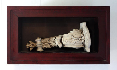 Photo of plaster sculptural ornament laying on it's side in a wooden shadowbox hanging on the wall