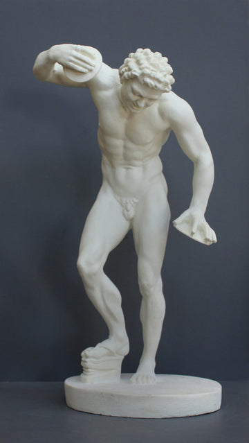 Photo with gray background of plaster cast sculpture of male faun or satyr dancing with instruments attached to his hands