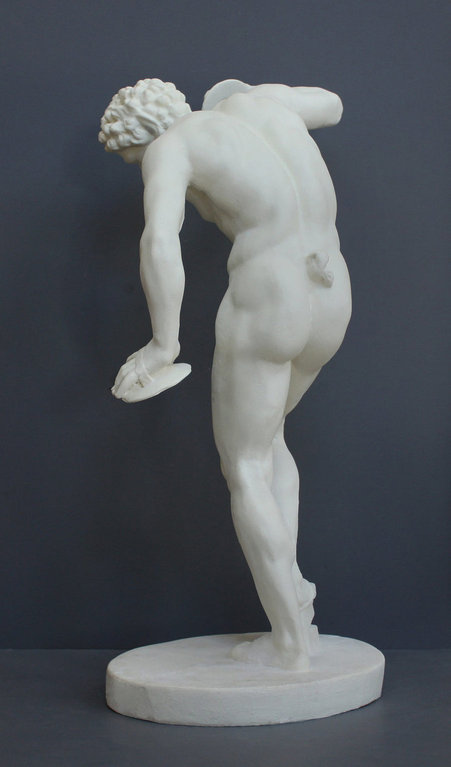 Photo with gray background of plaster cast sculpture of male faun or satyr from the back dancing with instruments attached to his hands