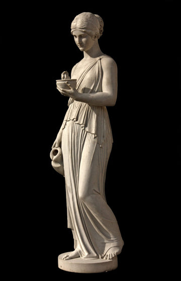 photo with black background of plaster cast sculpture of goddess Hebe in robes standing and holding a jug in right hand at her side and a bowl with a flame in left hand raised in front of her