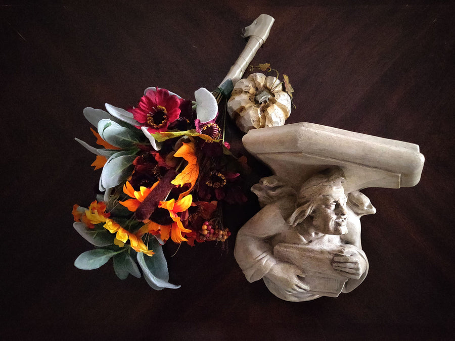 photo of plaster cast sculpture of architectural bracket on a dark table next to fall flowers and a pumpkin