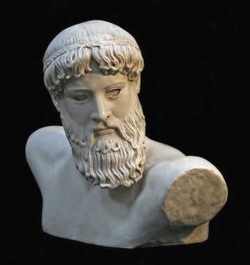 Photo with black background of plaster cast sculpture of male bust, namely the god Poseidon, with curly hair and beard and fragmented arms raised