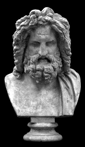 Photo with black background of plaster cast sculpture of male bust, namely the god Zeus, with curly hair and beard and robe on left shoulder