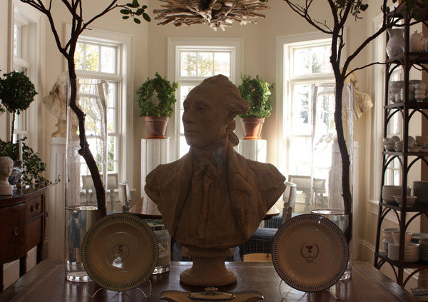 photo of plaster cast of male bust sculpture, namely Lafayette, in uniform on a table with decorative dishes and other furniture, dishes, plants, and bay windows behind