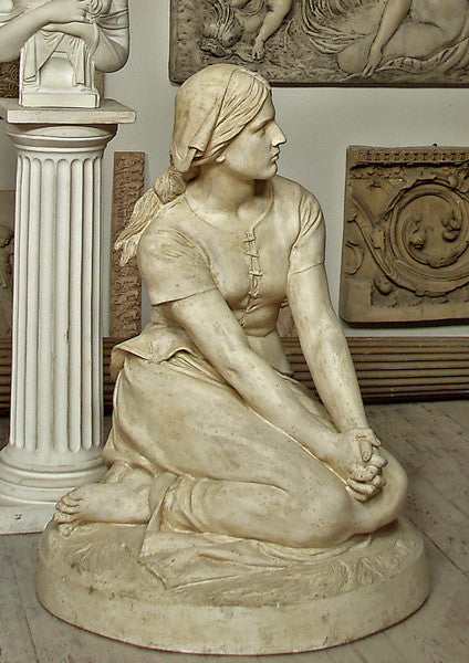 photo of plaster cast sculpture of Joan of Arc kneeling with hands on lap in a gallery with other plaster casts