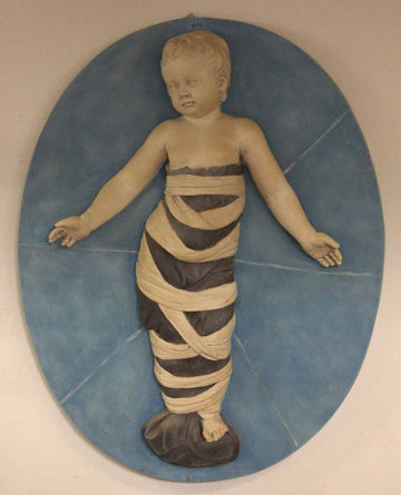 photo of plaster cast relief of child with mummy-like wrappings on a blue oval background on a tan-colored wall