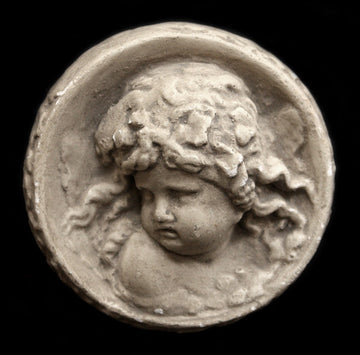 Photo of small round plaster sculpture medallion of head of an infant on a black background