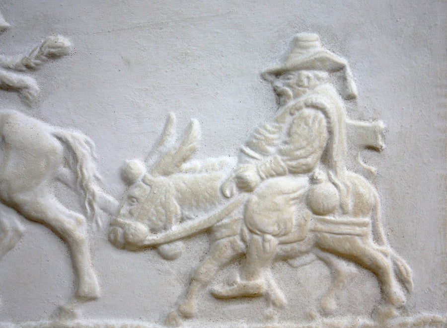 closeup photo of plaster cast relief sculpture of man riding donkey in profile