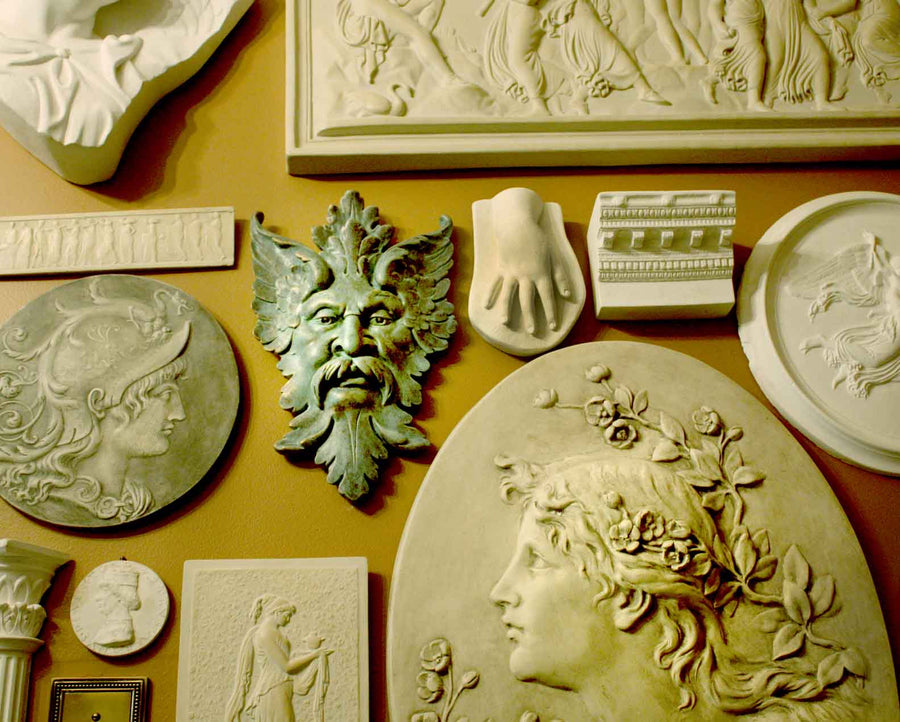 photo of plaster cast sculpture reliefs on orange-brown wall, including verdigris-colored relief of moustached man's face made of leaves