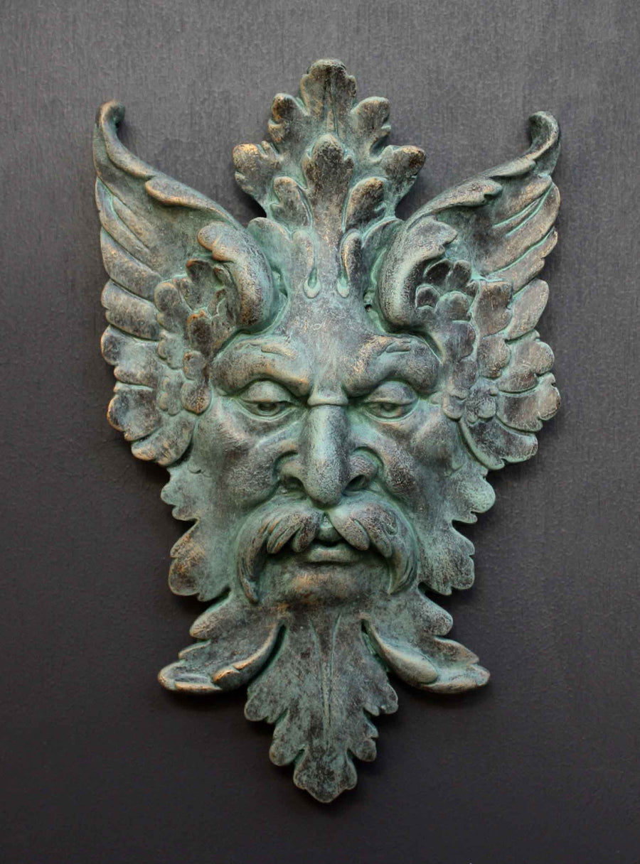 photo of verdigris-colored plaster cast sculpture relief of moustached man's face made of leaves with gray background
