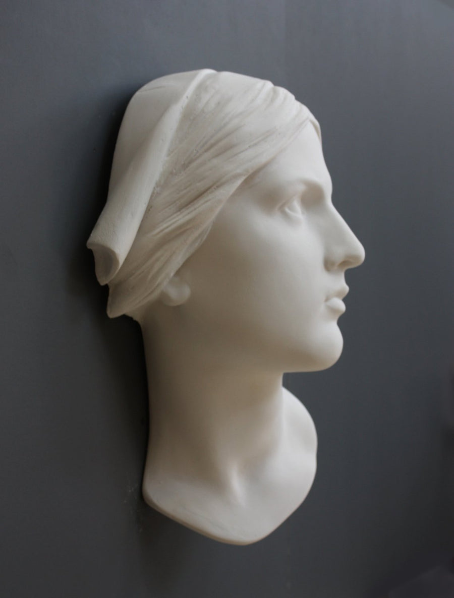 photo with gray background of plaster cast sculpture of Joan of Arc's face and portion of kerchief on head