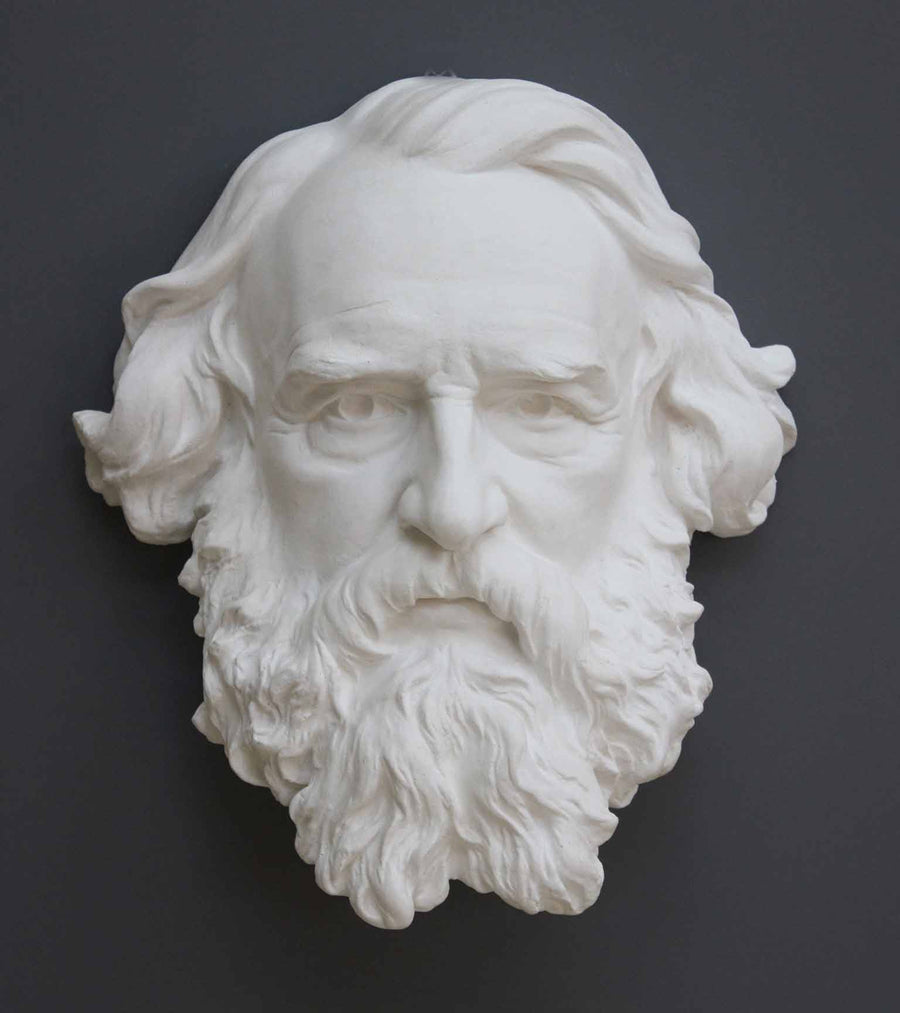 photo of plaster cast of man's head, namely Longfellow, with long hair and curly beard on gray background