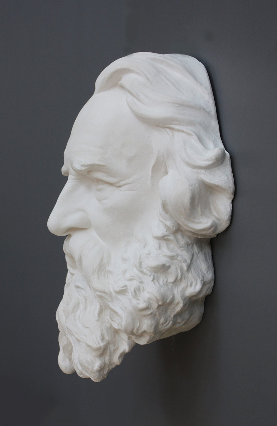 photo of plaster cast of man's head on gray background from side view