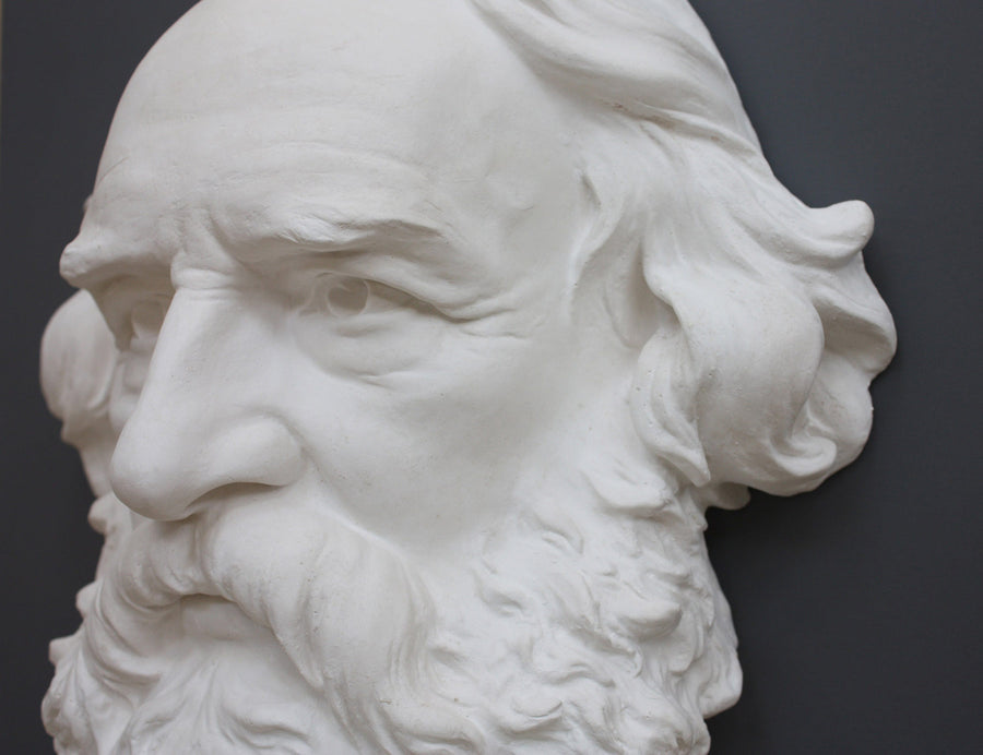 closeup photo of plaster cast of man's head, namely Longfellow, with long hair and curly beard on gray background