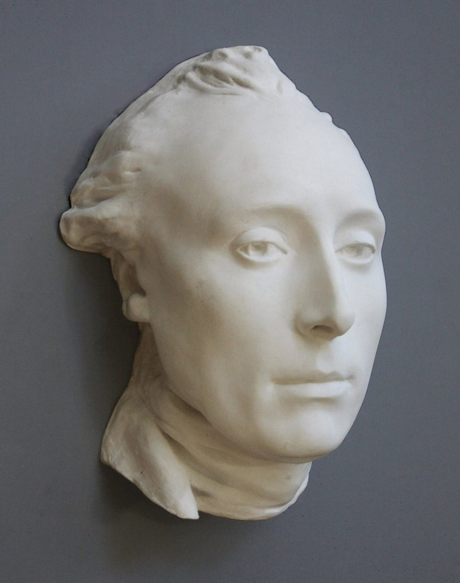 photo with gray background of plaster cast of male head with neckerchief
