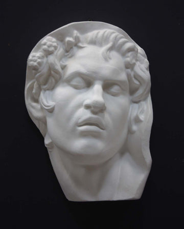 photo of plaster cast of sculpture of face of Sleeping Faun with two flowers in curly hair on dark gray background