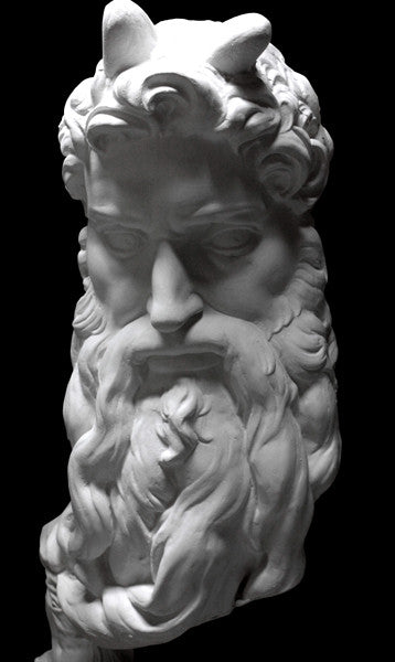 photo of plaster cast bust of man, namely Moses, with curly hair and so-called horns and long beard on black background