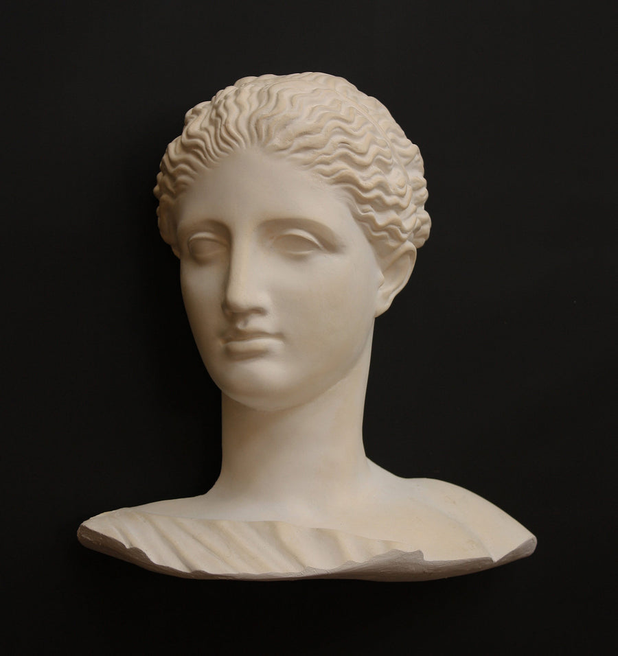photo of plaster cast of ancient female bust, namely the goddess Diana, with a black background
